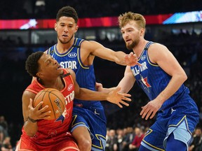 Team Giannis guard Kyle Lowry, left, of the Raptors drives against Team LeBron forward Domantas Sabonis, right, of the Pacers and Devin Booker of the Suns during the 2020 NBA All-Star Game at United Center in Chicago, Feb. 16, 2020.