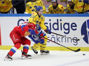 Russia's Vasily Podkolzin (L) and Sweden's Jesper Sellgren fight for the puck during the Beijer Hockey Games (Euro Hockey Tour) ice hockey match between Sweden and Russia in Malmo on February 13, 2021. (Photo by Anders Bjuro / TT NEWS AGENCY / AFP) / Sweden OUT (Photo by ANDERS BJURO/TT NEWS AGENCY/AFP via Getty Images) ORG XMIT: 0