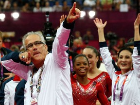 In this file photo taken on July 31, 2012, US women gymnastics team's coach John Geddert celebrates with the rest of the team after the US won gold in the women's team artistic gymnastics event at the London Olympic Games.