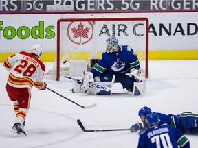 Feb 15, 2021; Vancouver, British Columbia, CAN; Calgary Flames forward Elias Lindholm (28) scores on Vancouver Canucks goalie Thatcher Demko (35) in the second period at Rogers Arena. Mandatory Credit: Bob Frid-USA TODAY Sports