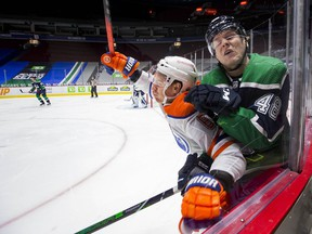 Edmonton Oilers forward Tyler Ennis (63) checks Vancouver Canucks defenceman Olli Juolevi (48) in the first period at Rogers Arena.