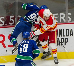 VANCOUVER, BC - February 11, 2021  - Vancouver Canucks Justin Bailey is hit by Calgary Flames Milan Lucic , injuring Bailey's shoulder/arm during NHL action at Rogers Arena in Vancouver, BC, February 11, 2021.   Photo by Arlen Redekop / Vancouver Sun / The Province News (PNG) (story by reporter) [PNG Merlin Archive]
