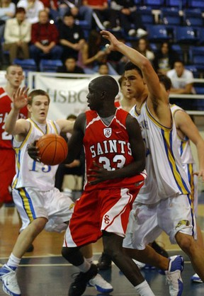 Bol Kong of the St. George Saints battles Rob Sacre and the Handsworth Royals at the HSBC Classic Seniors Basketball Championship Game at UBC's War Memorial Gym. St. George won 57-55.