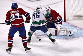 Vancouver Canucks left wing Antoine Roussel gets off a shot against Montreal Canadiens goaltender Jake Allen as Montreal winger Alexander Romanov looks on in the first.