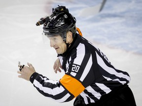 Referee Tim Peel wears a helmet camera during action between the Calgary Flames and Vancouver Canucks in Calgary on Wednesday, Oct. 8, 2014.