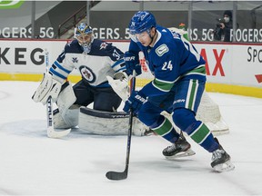 Winnipeg Jets goalie Connor Hellebuyck (37) defends the goal against Vancouver Canucks forward Jimmy Vesey (24) in the second period at Rogers Arena.