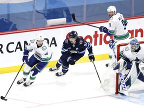 Canucks centre Elias Pettersson shields the puck from a chasing Mark Scheifele of the Winnipeg Jets while goalie Thatcher Demko holds his post during their March 1, 2021 NHL game in Winnipeg.