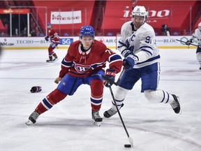 Jake Evans #71 of the Montreal Canadiens handles the puck against John Tavares #91 of the Toronto Maple Leafs during the third period at the Bell Centre on April 28, 2021 in Montreal, Canada.