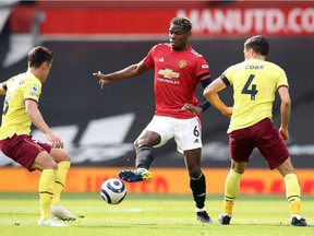 Paul Pogba of Manchester United is challenged by Ashley Westwood of Burnley and Jack Cork of Burnley during the Premier League match between Manchester United and Burnley at Old Trafford on April 18, 2021 in Manchester, England.