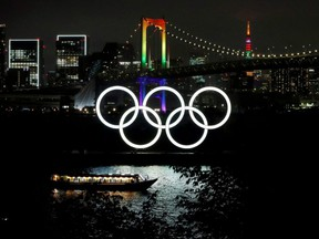 The Rainbow Bridge and Tokyo Tower are illuminated with Olympic colours to mark 100 days countdown to the Tokyo 2020 Olympics that have been postponed to 2021 due to the COVID-19 outbreak, in Tokyo, Japan, Wednesday, April 14, 2021.