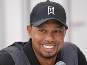 In this file photo US golfer Tiger Woods smiles while speaking to the press at the Congressional Country Club in Bethesda, Maryland on June 24, 2014.