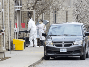 Pushing an empty stretcher, a man enters Anson Place Care Centre in Hagersville, Ont., to remove a body from the long term care and retirement home, April 12, 2020.