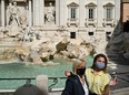 Tourists wearing a face pose by the Trevi Fountain in downtown Rome.