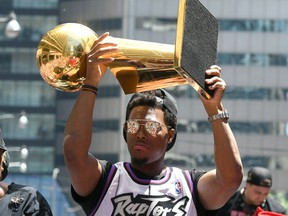 Raptors guard Kyle Lowry shows off the Larry O'Brien trophy to fans during a parade through downtown Toronto to celebrate their NBA title.