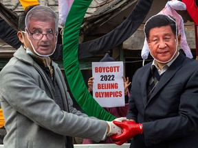 Protesters wear masks of IOC President Thomas Bach, left, and Chinese President Xi Jinping during a demonstration against the 2022 Beijing Winter Olympics, in Dharmsala, India, in a file photo from Feb. 3, 2021.