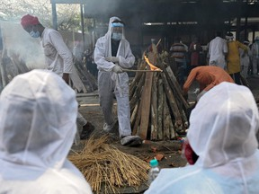 A family member (centre) wearing protective gear performs the last rites of a victim who died of COVID-19 at a crematorium in Ghazipur, India, Saturday, May 1, 2021.
