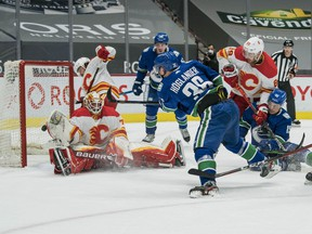 Canucks rookie Nils Höglander scores in the first period, his 13th goal of the season, on Flames netminder Louis Domingue on Tuesday at Rogers Arena.