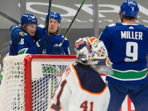Vancouver Canucks Brock Boeser and Nils Hoglander look towards J.T. Miller after Boeser scored in first period against the Edmonton Oilers at Rogers Arena on Tuesday night.