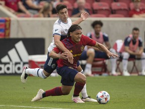 Marcelo Silva of Real Salt Lake is tackled by Brian White of the Vancouver Whitecaps FC during their game June 18, 2021 at Rio Tinto Stadium in Sandy, Utah.