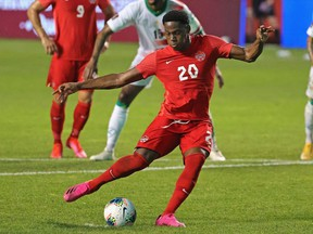 Jonathan David #20 of Canada scores his third goal of the match on a penalty kick against Suriname during a FIFA World Cup Qualifier at SeatGeek Stadium on June 08, 2021 in Bridgeview, Illinois.