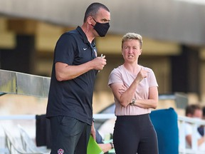 Canada head coach Bev Priestman, right, speaks to assistant Michael Norris during a game in Cartagena, Spain on June 11, 2021. Canada tied Brazil 0-0 on Monday.