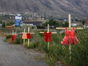 Children's red dresses are staked along a highway near the former Kamloops Indian Residential School where flowers and cards have been left as part of a growing makeshift memorial to honor the 215 children whose remains have been discovered buried near the facility, in Kamloops, British Columbia, Canada, on June 2, 2021.
