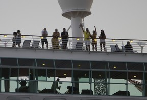 Passengers wave as the Royal Caribbean Freedom of the Seas gets underway through the Government Cut shipping channel at PortMiami on June 20, 2021.
