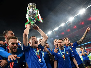 LONDON, ENGLAND - JULY 11: (L-R) Leonardo Spinazzola, Rafael Toloi, Andrea Belotti and Jorginho of Italy celebrate with The Henri Delaunay Trophy following their team's victory in the UEFA Euro 2020 Championship Final between Italy and England at Wembley Stadium on July 11, 2021 in London, England.