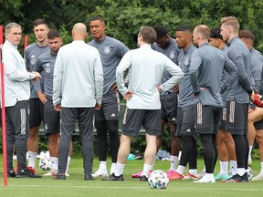 Stefan Kuntz, left, head coach of the German Olympic football team, talks with his players during a training session in Frankfurt am Main, western Germany, on July 13, 2021.
