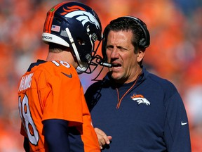 Peyton Manning, left, of the Denver Broncos speaks to offensive coordinator Rick Dennison in the first half against the New England Patriots in the AFC Championship game at Sports Authority Field at Mile High on Jan. 24, 2016 in Denver.