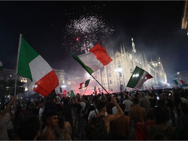 Supporters of the Italian national football team celebrate after Italy beat England 3-2 on penalties to win the UEFA EURO 2020 final football match between England and Italy in Piazza del Duomo in Milan on July 11, 2021.