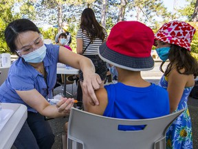Ada Zeng of Coastal Health gives a COVID-19 vaccination to Joseph, 13. After taking a spin on the AtmosFear and snacking on hotdogs and mini donuts, people visiting Playland this weekend were invited to stop by the one-immunization clinic.