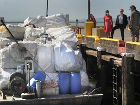 Officials look over a barge stacked with bales of plastic waste at the official opening of Ocean Legacy Foundation's new plastic processing facility at the Steveston Harbour in Richmond.