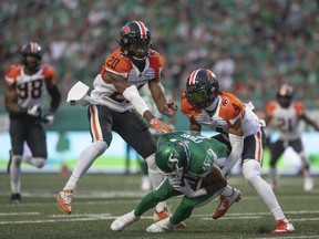 Lions defenders Garry Peters (left) and Bo Lokombo wrap up Roughriders receiver Shaq Evans after he gathers in the ball during the previous game that the teams faced each other, a 33-29 Riders win that opened both teams' CFL season in Regina on Aug. 6.