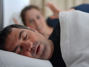 Woman suffers from her male partner snoring in bed.