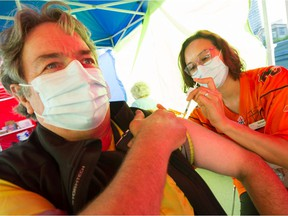 Ray Frison gets his vaccine shot from nurse Stephanie McLeod  and a free pass to a game, prior to the CFL game to start between BC Lions and Edmonton Elks at BC Place in Vancouver, BC, August 19, 2021.