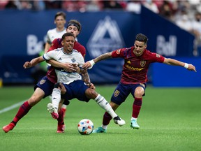 Vancouver Whitecaps' Bruno Gaspar, front left, is grabbed by Real Salt Lake's Nick Besler, back left, as he and Jonathan Menendez, right, vie for the ball during first-half MLS soccer action at B.C. Place Stadium last week.