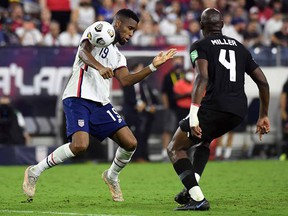 United States midfielder Brenden Aaronson (11) plays the ball off his shoulder against Canada defender Kamal Miller (4) during their CONCACAF World Cup Qualifier at Nissan Stadium.