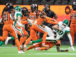 Saskatchewan Roughriders' Kian Schaffer-Baker, front right, is tackled by B.C. Lions' Marcus Sayles during the first half of a CFL football game in Vancouver, on Friday, Sept. 24, 2021.