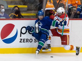 Canucks defenceman Oliver Ekman-Larsson (left) and Flames forward Luke Philp collide along the boards on Monday in Abbotsford. 'It's nice to see how fast he's playing, moving the puck so well and how physical he is. He looks really engaged and looks like the Oliver I know,' teammate Conor Garland — who came to the Canucks with Ekman-Larsson from Arizona —says of his fellow Canuck.