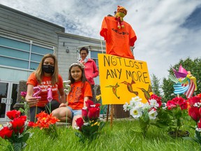 Seven-year-old Eliya Sparrow and Karen Grant (front-left) wearing orange shirts in Vancouver in May 2021, in tribute to those who were buried at the Kamloops residential school.