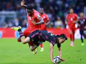 Alphonso Davies of Canada battles for possesion with Hirving Lozano of Mexico during the match between Mexico and Canada as part of the Concacaf 2022 FIFA World Cup Qualifier at Azteca Stadium on October 07, 2021 in Mexico City, Mexico.