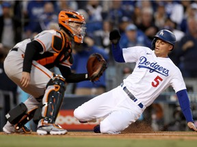 Corey Seager #5 of the Los Angeles Dodgers scores against Buster Posey #28 of the San Francisco Giants on a double by Trea Turner #6 during the first inning in game 4 of the National League Division Series at Dodger Stadium on October 12, 2021 in Los Angeles, California.