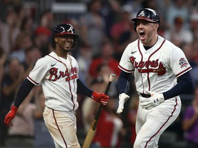 Atlanta Braves first baseman Freddie Freeman (right) celebrates with second baseman Ozzie Albies (left) after hitting a home run against the Milwaukee Brewers at Truist Park.