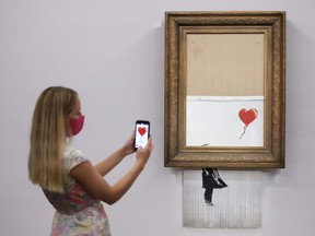 A gallery assistant poses by 'Love is in the Bin', an artwork by Banksy, which will be for sale in an auction, at Sotheby's in London, Britain, September 3, 2021.