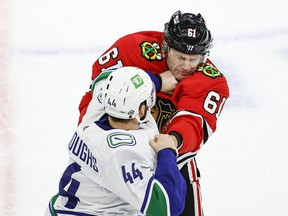 Vancouver Canucks defenceman Kyle Burroughs (44) fights with Chicago Blackhawks defenxeman Riley Stillman (61) during the first period at United Center.