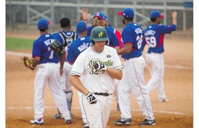Australia infielder James Brownlow leaves the field after he and his team are defeated by team Dominican Republic during the Men's World Softball Championships at Bob Van Imp park on Monday.