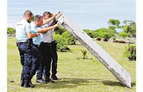 French police officers inspect what is believed to be a 'flaperon' from the trailing edge of a Boeing 777 wing Wednesday in Saint-Andre on the French island of Reunion.
