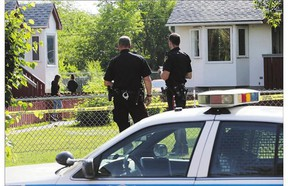 Police investigate a double shooting at a small housing complex in the 300 block of Avenue R South Monday.