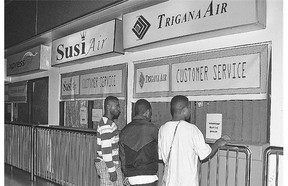 Relatives of passengers on the missing Trigana Air Service flight stand at the closed offices at Sentani airport Sunday.